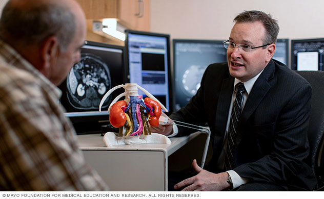 A radiologist uses a 3D model to help a man understand his diagnosis.